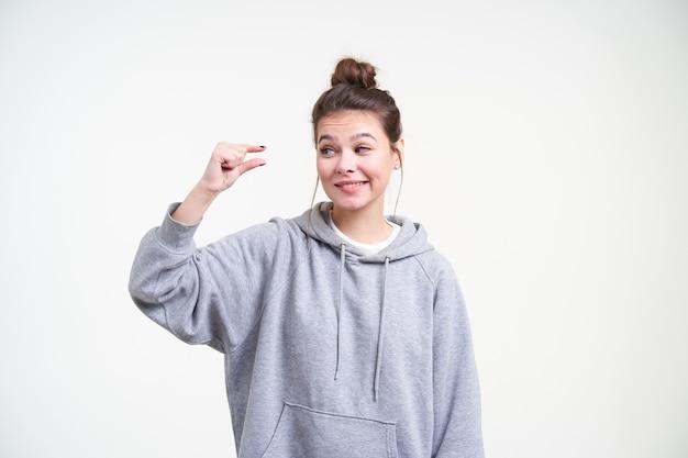 Mulher jovem e adorável confusa de cabelos compridos com maquiagem natural, parecendo ironicamente em sua mão enquanto mostra o tamanho pequeno com os dedos, isolado sobre fundo branco