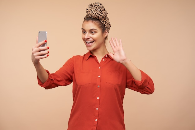 Mulher jovem e adorável de cabelos castanhos feliz com fita na cabeça, sorrindo alegremente na frente do telefone e levantando a mão em um gesto de olá durante a videochamada, posando sobre uma parede bege