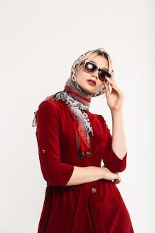 Mulher jovem e adorável elegante com lábios sensuais em elegantes óculos de sol com vestido vermelho em poses de lenço de leopardo perto de parede vintage. modelo de moda sensual garota glamourosa. senhora moderna. estilo retrô.
