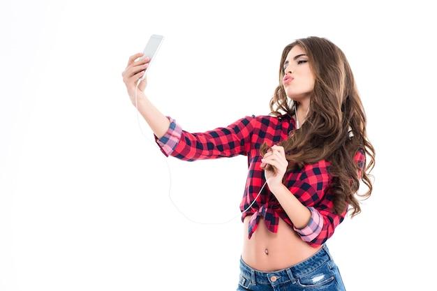 Mulher jovem e adorável fazendo careta de pato e tirando selfie com o celular na parede branca