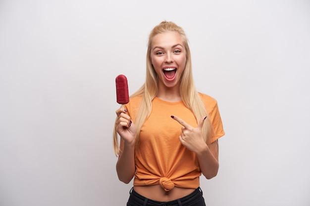 Mulher jovem e adorável loira com um penteado casual apontando com o dedo indicador no sorvete de frutas vermelhas na mão, olhando com alegria para a câmera com a boca aberta, isolado sobre um fundo branco