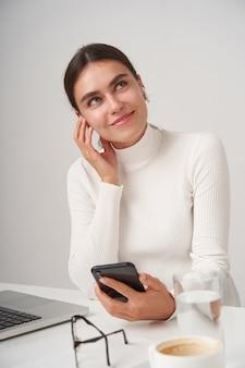 Mulher jovem e adorável morena satisfeita olhando sonhadoramente para cima enquanto ouve música com seus fones de ouvido e smartphone, vestindo roupas formais enquanto está sentada na parede branca
