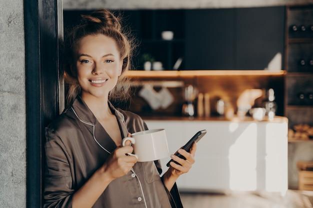 Mulher jovem e adorável tomando seu café da manhã enquanto verifica novos e-mails e notificações no smartphone em pé na cozinha sorrindo amplamente após acordar, passando o fim de semana em casa