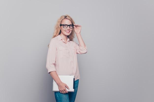 Mulher jovem e adorável usando óculos formais casuais segurando um tablet