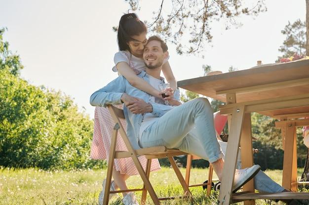 Mulher jovem e afetuosa feliz com um copo de vinho tinto abraçando seu namorado sorridente, sentado na cadeira ao lado da mesa servida ao ar livre