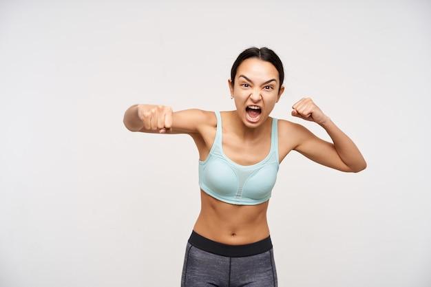 Mulher jovem e agressiva de cabelos castanhos com penteado casual boxeando com punhos erguidos e fazendo caretas enquanto grita furiosamente, posando sobre uma parede branca