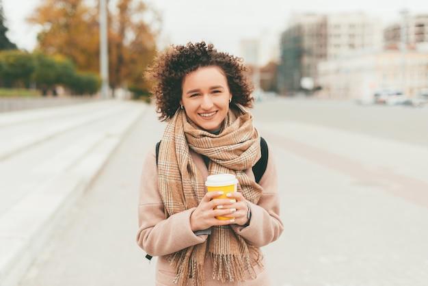 Mulher jovem e alegre, casual, caminhando na rua e segurando uma xícara de café quente