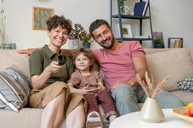 Mulher jovem e alegre com controle remoto, o marido e o filho pequeno estão sentados no sofá confortável em frente à tv em casa