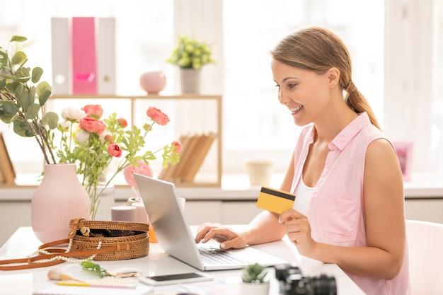 Mulher jovem e alegre com um cartão de plástico olhando para a tela do laptop enquanto insere dados pessoais para pagar o pedido na loja online