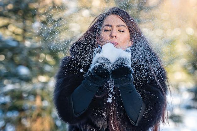 Mulher jovem e alegre com um casaco de pele quente, aproveitando um dia de inverno no bosque nevado