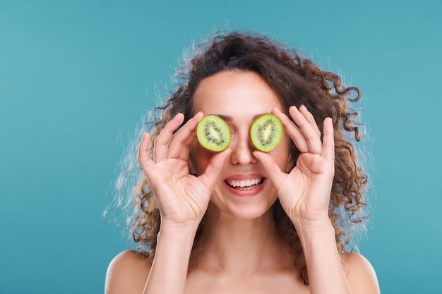 Mulher jovem e alegre com um sorriso largo segurando duas metades de kiwi fresco e suculento perto dos olhos