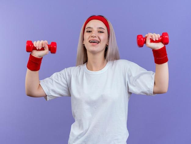 Mulher jovem e alegre e esportiva com aparelho nos braços e pulseira ereta com as mãos levantadas segurando halteres isolado na parede roxa