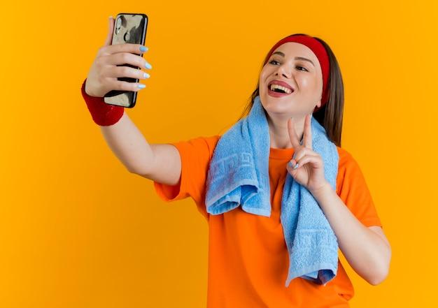 Mulher jovem e alegre e esportiva usando bandana e pulseiras com uma toalha no pescoço, fazendo o sinal da paz, tomando selfie