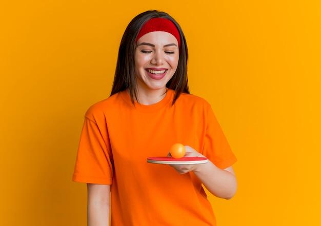 Mulher jovem e alegre e esportiva usando bandana e pulseiras segurando e olhando para uma raquete de pingue-pongue com uma bola