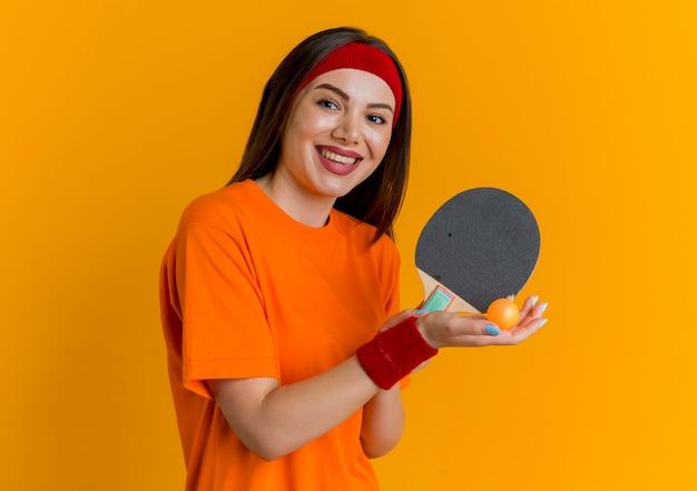 Mulher jovem e alegre e esportiva usando bandana e pulseiras segurando uma raquete de pingue-pongue e bola olhando