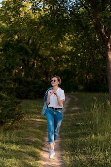 Mulher jovem e alegre em óculos de sol da moda, caminhando na natureza em um lindo dia