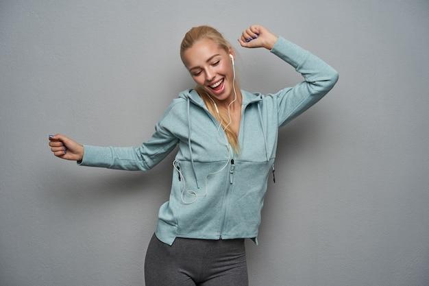 Mulher jovem e alegre, esportiva, com longos cabelos loiros, ouvindo música em fones de ouvido e dançando alegremente com as mãos levantadas sobre um fundo cinza claro, vestindo blusa hortelã, casaco e leggins cinza