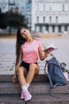 Mulher jovem e alegre fazendo anotações enquanto está sentada nos degraus da rua
