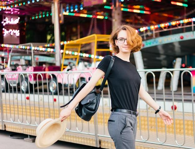 Mulher jovem e alegre hippie de óculos e chapéu no parque de diversões