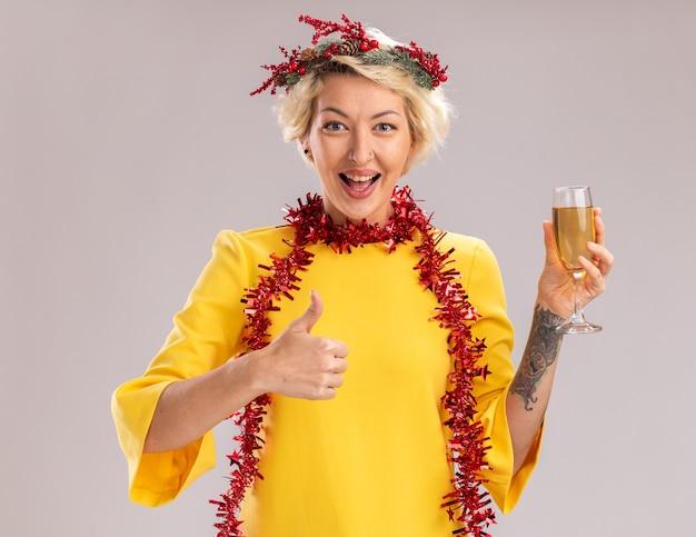 Mulher jovem e alegre, loira, usando a coroa da cabeça de natal e guirlanda de ouropel em volta do pescoço, segurando uma taça de champanhe, olhando para a câmera mostrando o polegar isolado no fundo branco
