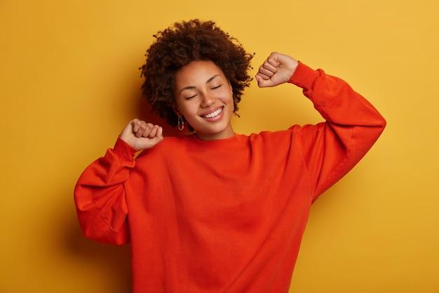 Mulher jovem e alegre, relaxada e cacheada, com um sorriso feliz, mantém ambas as mãos levantadas, usa um macacão casual, tem os olhos fechados, modelos contra um fundo amarelo