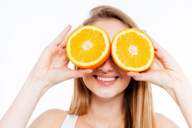 Mulher jovem e alegre segurando duas metades de laranja contra os olhos sobre um fundo branco