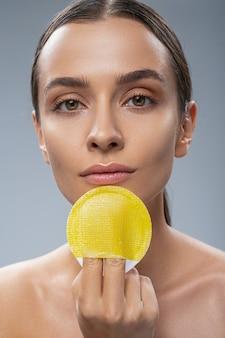 Mulher jovem e alegre segurando uma esponja para cuidar do rosto