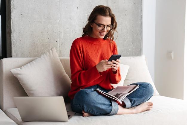 Mulher jovem e alegre vestida casualmente com fones de ouvido, sentada em um sofá em casa, estudando com o computador laptop, segurando um telefone celular