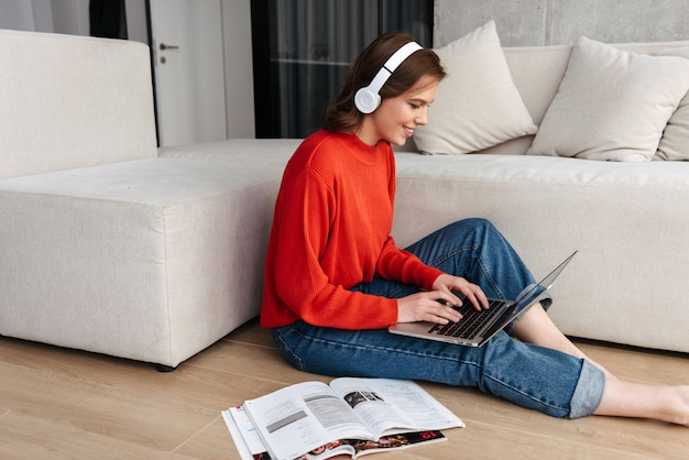 Mulher jovem e alegre vestida casualmente com fones de ouvido, sentada no chão em casa, estudando com um laptop