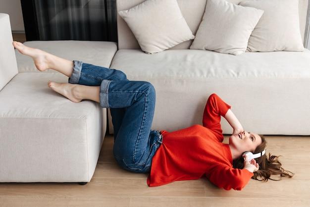 Mulher jovem e alegre, vestida de maneira casual, deitada no chão em casa, ouvindo música com fones de ouvido