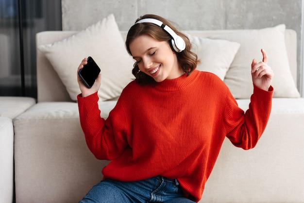 Mulher jovem e alegre, vestida de maneira casual, sentada no chão de casa, ouvindo música com fones de ouvido