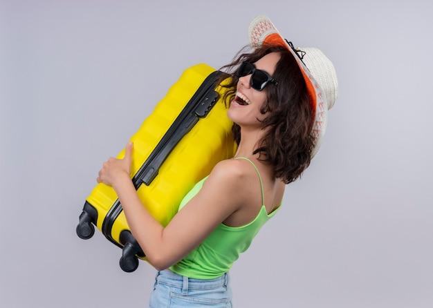 Mulher jovem e alegre viajante usando chapéu e óculos escuros e segurando a mala em pé na vista de perfil na parede branca isolada