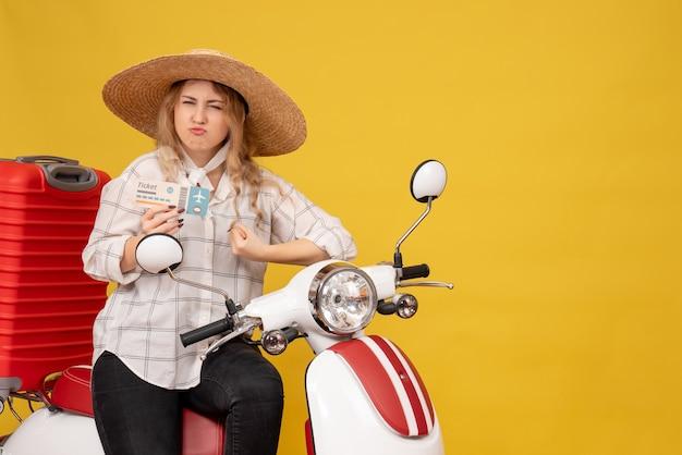 Mulher jovem e ambiciosa de chapéu, sentada em uma motocicleta segurando uma passagem e ouvindo a última fofoca no amarelo