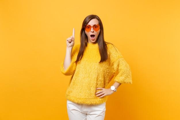 Mulher jovem e animada chocada em suéter, óculos coração laranja apontando o dedo indicador para cima no espaço da cópia isolado em fundo amarelo brilhante. emoções sinceras de pessoas, conceito de estilo de vida. área de publicidade.
