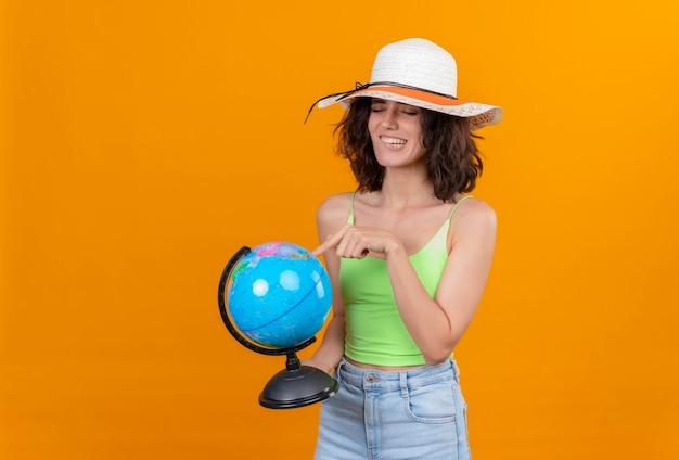 Mulher jovem e animada com cabelo curto e top verde curto e chapéu de sol apontando para um globo com o dedo indicador