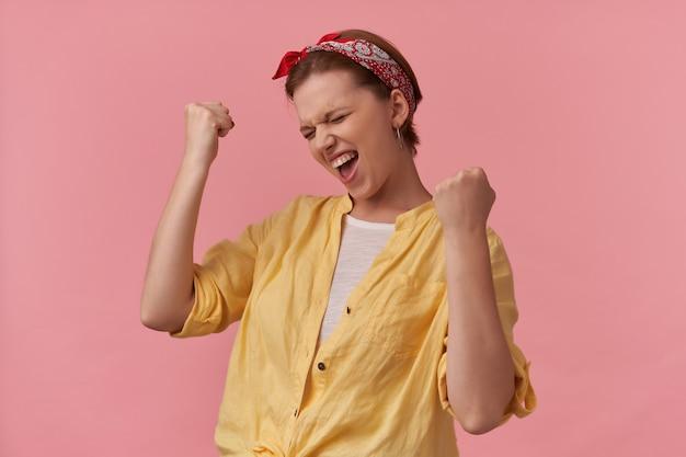 Mulher jovem e animada com camisa amarela e bandana na cabeça, mostrando o gesto do vencedor e comemorando a vitória sobre a parede rosa