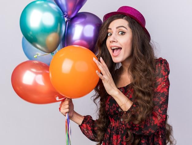 Mulher jovem e animada com um chapéu de festa em pé na vista de perfil, segurando balões, tocando um olhando para a frente, isolado na parede branca