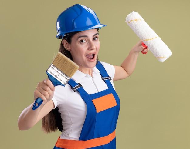 Mulher jovem e animada construtora de uniforme segurando a escova giratória e o pincel isolado na parede verde oliva