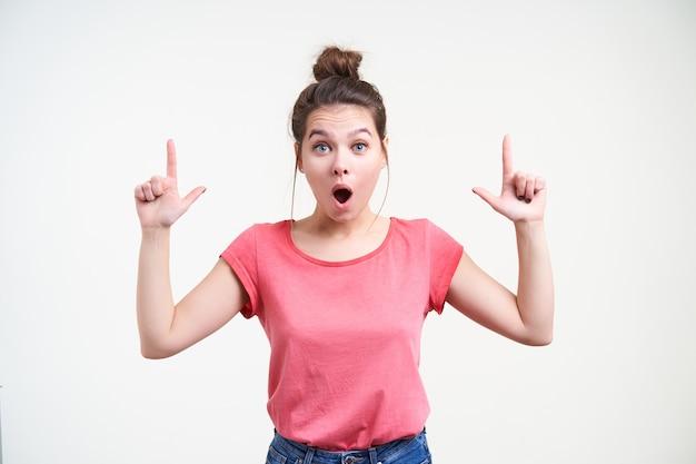 Mulher jovem e animada de cabelos muito compridos com penteado em forma de coque, mantendo as mãos levantadas enquanto se mostra atordoada para cima com os indicadores, em pé sobre um fundo branco