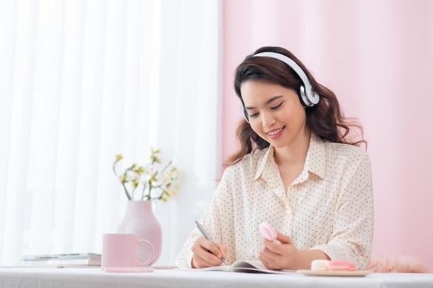 Mulher jovem e animada de óculos ouvindo música no escritório e tendo uma ideia