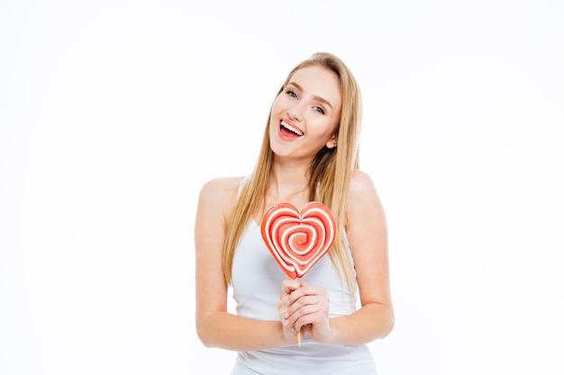 Mulher jovem e animada feliz em pé e segurando um pirulito em forma de coração sobre fundo branco