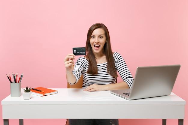 Mulher jovem e animada segurando um cartão de crédito enquanto está sentado trabalhando na mesa branca com um laptop pc contemporâneo
