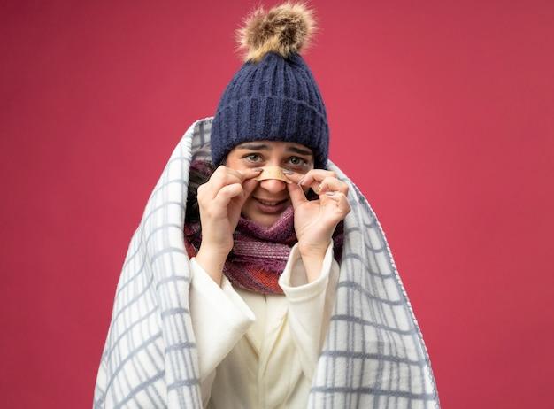 Mulher jovem e ansiosa com um manto de inverno, um chapéu e um cachecol embrulhado em xadrez, olhando para a frente, colocando gesso no nariz isolado na parede rosa