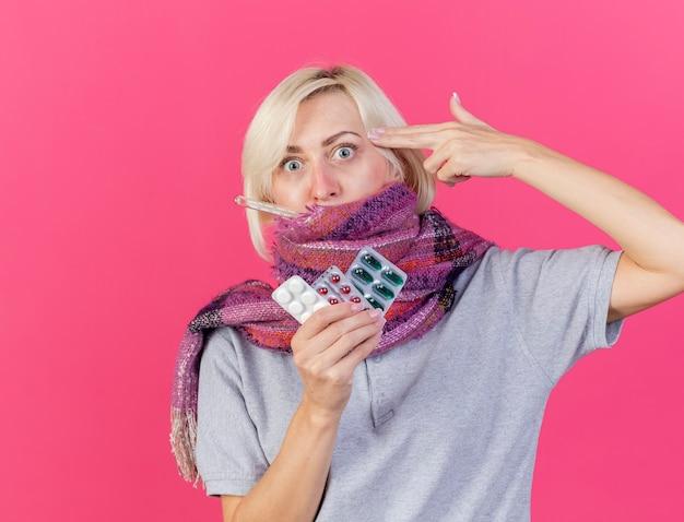 Mulher jovem e ansiosa, loira, eslava, usando lenço, gestos, arma, mão, sinal, colocando no templo, segurando pacotes de comprimidos médicos medindo a temperatura com termômetro na parede rosa