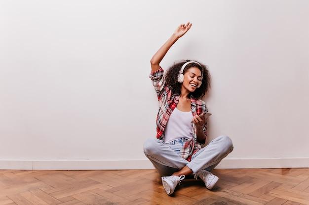 Mulher jovem e arrepiante sentada no chão ouvindo música. incrível garota africana posando com as pernas cruzadas enquanto desfruta da música favorita.