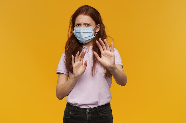 Mulher jovem e assustada e preocupada com máscara de proteção médica mantém as mãos na frente de si mesma e se defende da ameaça por causa da parede amarela