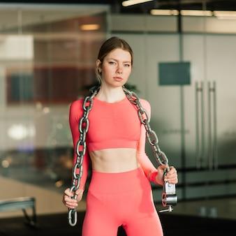 Mulher jovem e ativa em esportes fortes com corrente pesada na academia