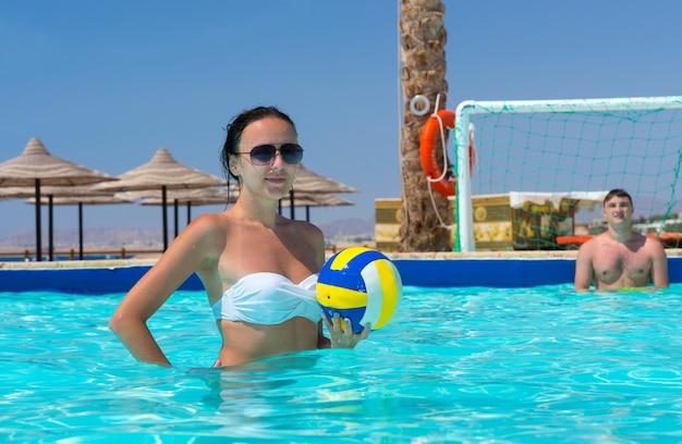 Mulher jovem e atlética segurando uma bola enquanto joga pólo aquático no hotel em um dia ensolarado de verão