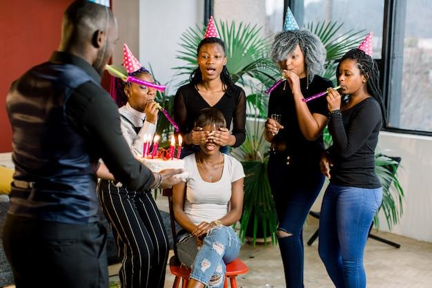 Mulher jovem e atraente africana com cabelos escuros, sentado na cadeira com seus amigos ao seu redor, comemorando e soprando suas velas de aniversário. um cara africano carrega bolo de aniversário com velas