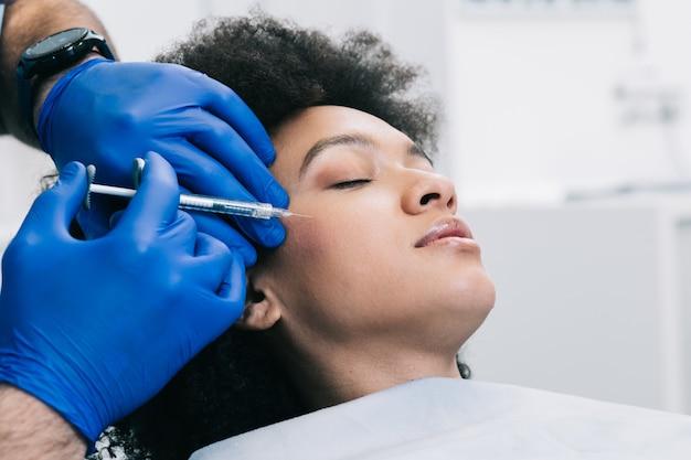 Mulher jovem e atraente africana está recebendo injeções faciais rejuvenescedoras. ela está calmamente sentada na clínica. a esteticista especialista está preenchendo as rugas femininas com ácido hialurônico.